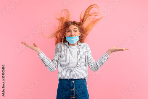 Photo shocked, agitated young woman in a medical protective mask on her face, screamin