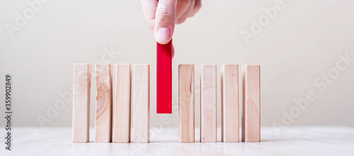 Cuadros en Lienzo Businessman hand placing or pulling Red wooden block on table