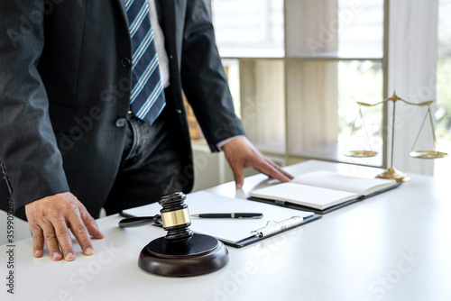 Fotografie, Tablou Male lawyer working with contract paper and Law books on table in courtroom