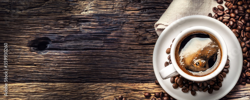 Obraz na plátně Black coffee in porcelain cup with scattered beans on rustic wooden table