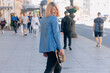Portrait of a young stylish woman walking along the street, dressed in a casual outfit