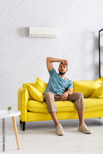 Selective focus of handsome man with hand near forehead feeling hot on couch at home