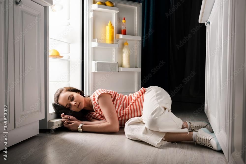 Fototapeta Young woman sleeping on floor near open fridge at night