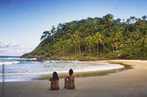 Dos mujeres sentadas contemplando el mar en una playa paradisiaca en Brasil Canvas Print