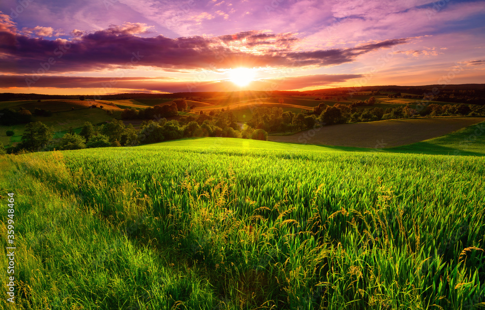 Fototapeta Sunset scenery on a green field with forests and hills on the horizon and the sky painted in gorgeous dramatic and emotional colors