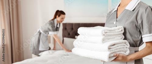 Chambermaid holding stack of fresh towels in hotel room, closeup view with space for text. Banner design