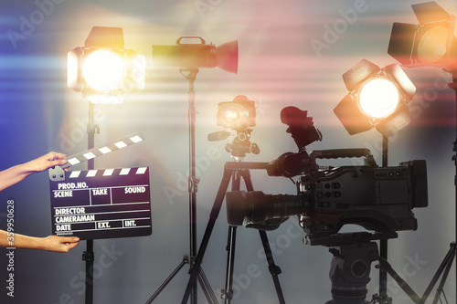 Carta da parati Woman with clapperboard near modern professional video camera in studio, closeup