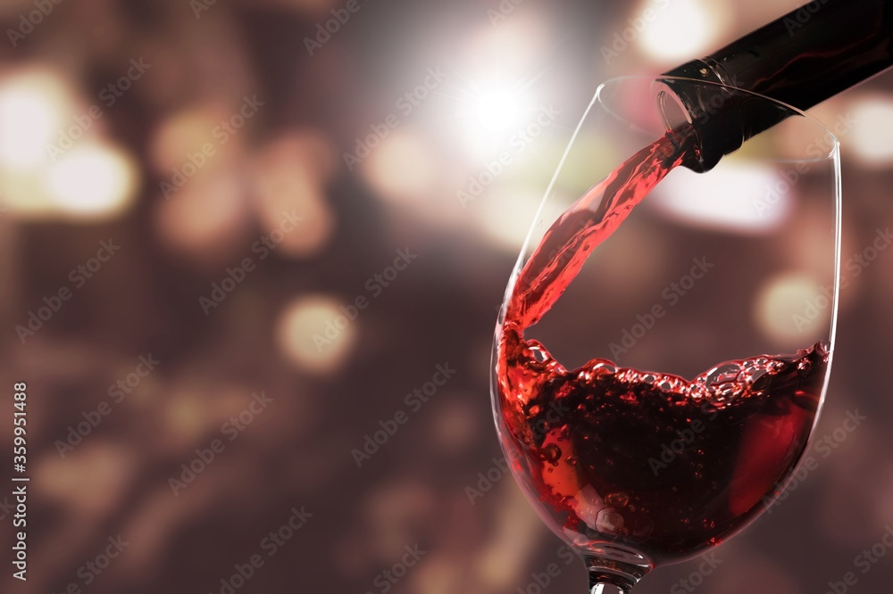 Fototapeta Red wine pouring from the bottle in glass