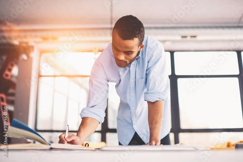 Skilled male afro american engineer thinking over blueprint improvement noting i Fototapet