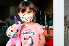 Portrait Of Girl With A Colorful Mask And A Unicorn Soft Toy