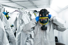 Sanitation Worker Wearing Gas Mask While Standing By Protective Coveralls In Locker Room