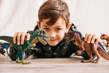 Smiling Little Boy Lying On The Floor Playing With Toy Dinosaurs