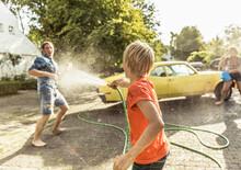 Friends Washing Yellow Vintage Car In Summer Having Fun
