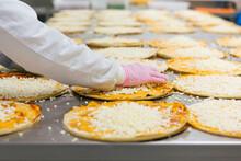 Woman Preparing Pizzas In Pizza Company
