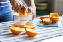 Woman Sqeezing Fresh Orange Ju...