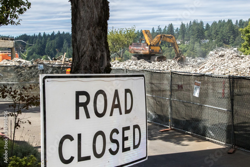 Photo Road closed sign adjacent to a construction site where a large track mounted backhoe is demolishing a building