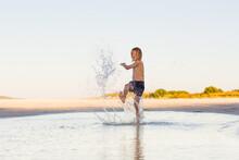 Kid Splashing Water On The Beach
