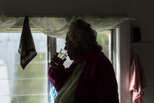 Elderly Woman In Dim Room Drin...
