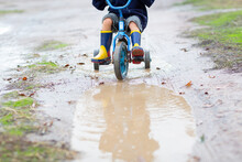 Child Riding Tricycle In Puddles