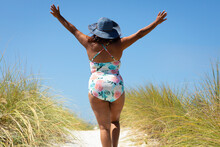 Woman Walking On Dune Path Wit...
