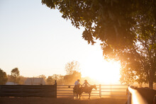 Two Horse Riders Meet At Stockyard Gate At Sunset