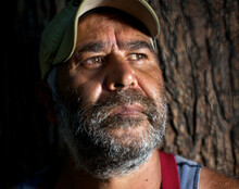 Aboriginal Man With Tree Trunk In Background