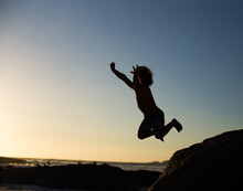Boy Jumping Off A Rock On The ...