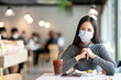 Young asian lady smiling with eyes under medical mask feeling safety relax at restaurant or canteen after coronavirus pandemic opening business eat lunch for breakfast with social distancing concept.