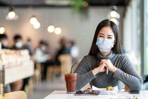 Valokuvatapetti Young asian lady smiling with eyes under medical mask feeling safety relax at restaurant or canteen after coronavirus pandemic opening business eat lunch for breakfast with social distancing concept