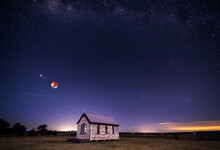 Blood Moon Setting, Planet Mars And A Universe Of Stars Shining Brightly Above The Rustic Chapel