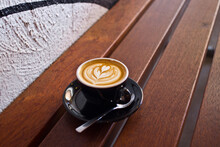 Single Flat White Coffee Sitting On A Wooden Table