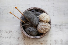 Knitting In Grey Woven Basket With Wooden Knitting Needles And Grey And Cream Wool