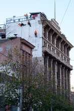 Workmen Suspended On Side Of Building Doing Repair Work