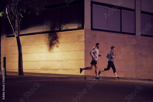 Two men fitness training in urban city at night - 360001200