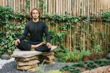 Man Meditating On Rocks In Gar...