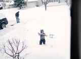 view of boy shoveling driveway