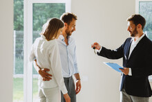 Real Estate Agent Handing Keys To Young Couple. Man And Woman In New Home