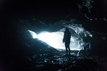 Silhouette Of An Explorer Woman Inside A Cave Next To The Sea