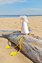 Funny Toy Seagull With Hat Sits On Log While Taking Sun Bath. Handmade Fabric Toys At Beach. DIY Concept