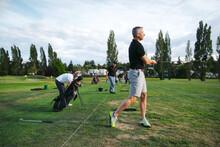 Man Practicing Golf At Driving Range.