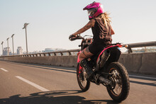 Woman Motorcyclist Riding Pink...