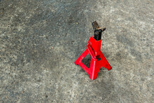 Red Axle Stand On Floor. Red High Lift Jack Stand On The Floor. Red Extendable Jack Stands Are Used To Lift Up And Support.