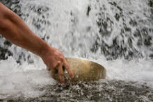 Hand Picking Up Water With A Big Tibetan Singing Bowl From A Waterfall.