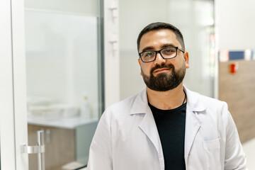 Portrait of handsome doctor. Cabinet background at hospital.