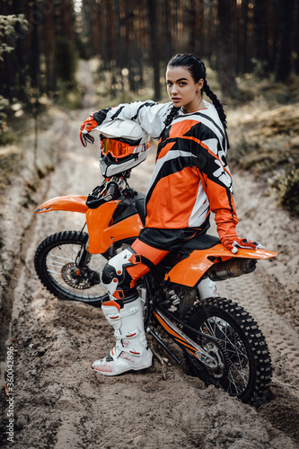 Fotografering Beautiful young brunette female racer riding motocross bike on a trail of sand i