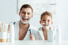 Selective Focus Of Cheerful Father And Son With Shaving Foam On Faces Holding Shaving Razors