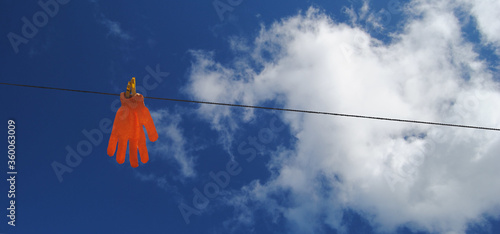 Luva em malha cor de laranja pendurada numa corda com molas amarelas a secar com Fototapeta