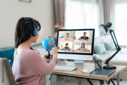 Fototapeta Asian woman teacher teaching geography via video conference e-learning and cheerful elementary school student looking at globe, Homeschooling and distance learning ,online ,education and internet