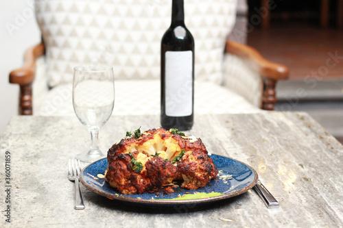 Photo chef monta plato gourmet colifror grande al horno  y vino tinto