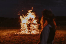 Woman Watching Midsummer Holidays Night Fire In Latvia
